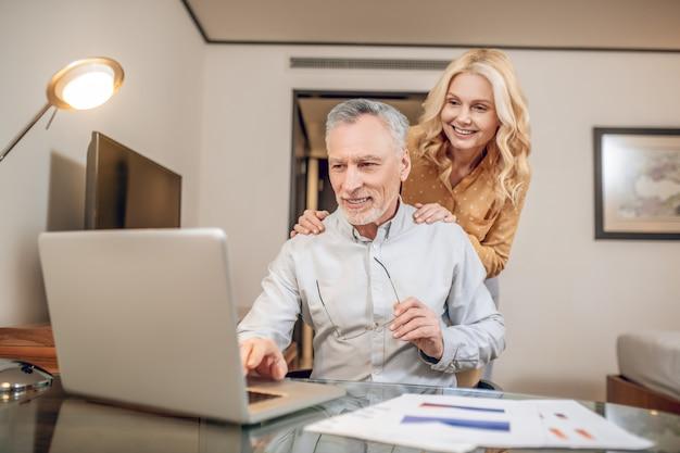 Пара. мужчина работает из дома, его жена стоит рядом с ним