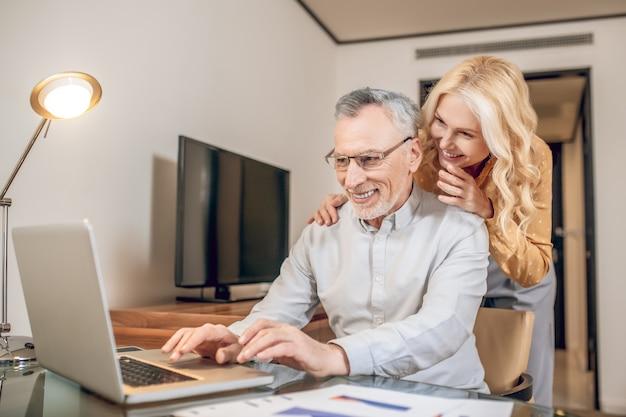 カップル。自宅で仕事をしている男性、彼の隣に立っている彼の妻
