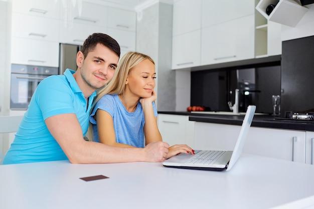 신용 카드를 소지 한 구매자 부부가 노트북으로 구매