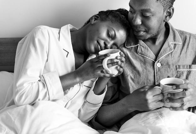 ベッドでコーヒーを持っているカップル