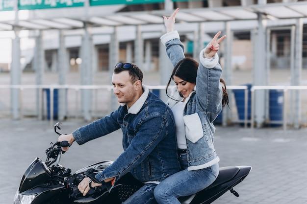 Влюбленная пара, парень и девушка на черном спортивном мотоцикле на первом свидании