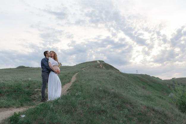 愛するカップル、白い服を着た妊娠中の妻が丘陵地帯を歩いています。どんよりした天気、