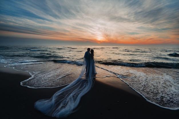 Влюбленная пара на закате на фоне моря, до неузнаваемости парочка