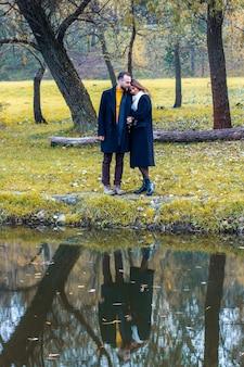 愛するカップルが湖の前で抱きしめる