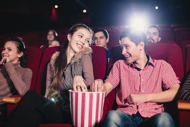 Влюбленная пара флиртует в кино и ест попкорн
