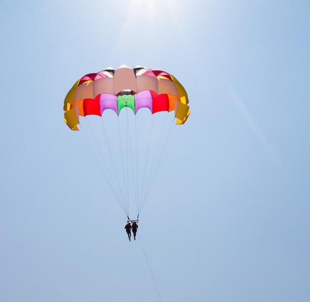 愛するカップルがヨットの後ろのパラシュートで空を横切って飛ぶ。危険な娯楽を愛する家族。南国の海の休日