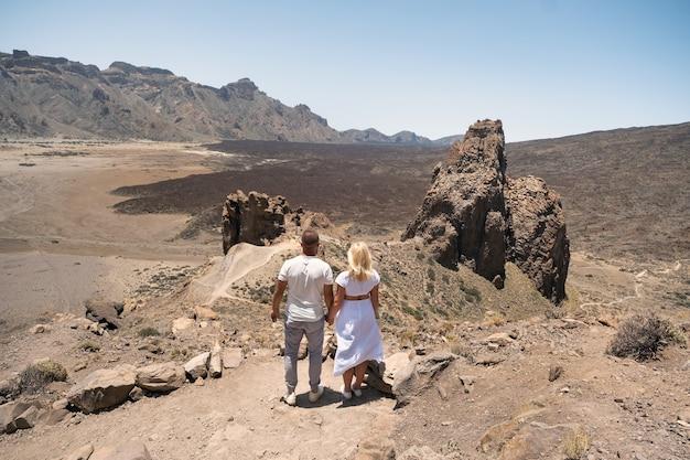 愛するカップルがテイデ火山の火口で手をつないでいる