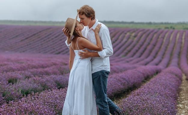 白い服を着たラベンダー畑で恋をしているカップル