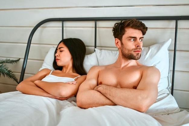 싸움에서 사랑에 빠진 커플. 한 젊은 부부가 침대에 누워 화를 내며 서로 멀어졌습니다.