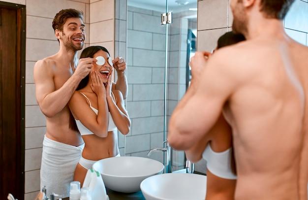 욕실에서 사랑에 빠진 커플은 즐겁습니다. 한 남자가 우스꽝스럽게 여자 친구에게 면화 디스크를 들고 있습니다. 메이크업 제거. 얼굴 피부 관리.