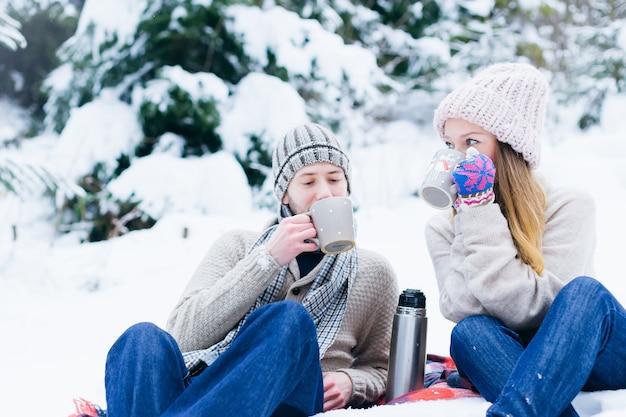 暖かい服を着て恋をしているカップルが雪の中で座ってカップから飲む