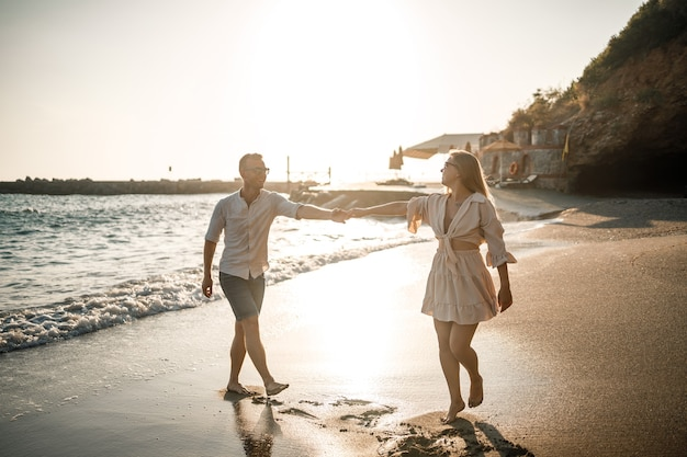 사랑에 빠진 커플이 바다 근처 해변을 걷고있다. 지중해에 의해 일몰에 젊은 가족. 여름 휴가 개념