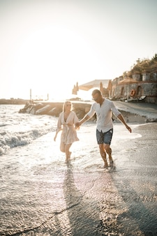 愛するカップルが海の近くのビーチを歩いています。地中海に沈む夕日の若い家族。夏休みのコンセプト