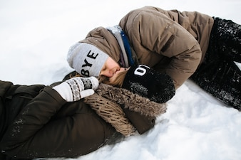 A couple in love lying in the snow and kissing. Winter love story.