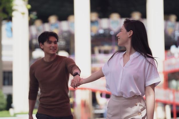 若い面白いと幸せな女性と遊園地の背景で歩いたり走ったりする男性を愛するカップル。