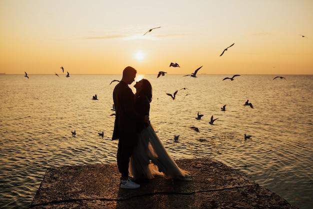 ビーチで恋をしているカップルが夕日に出会う