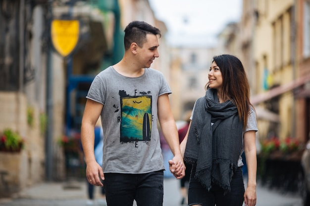 涼しい秋の朝、愛のカップルがゆっくりと街の通りを歩く