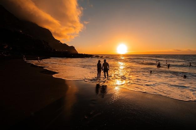 사랑에 빠진 부부는 저녁에 테네리페 섬의 아름다운 일몰을 바라보며 바다에 서 있습니다.스페인.