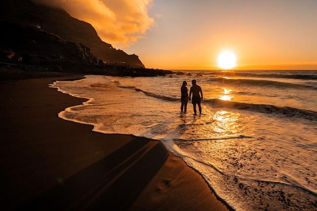 사랑에 빠진 커플은 테 네리 페 섬의 아름다운 일몰을 바라 보는 저녁에 바다에 선다. 스페인.