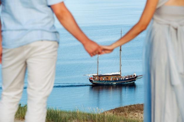 Влюбленная пара стоит на пляже в дюнах на фоне балтийского моря и корабля