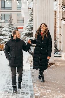 Влюбленная пара прогуливается по заснеженному городу, держась за руки