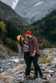 山を旅する恋のカップル。山で休んでいるカップル。山の中で楽しんでいる美しいカップル。男性と女性は自然を背景に抱きしめます。コピースペース