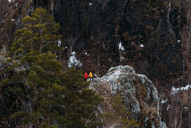 山を旅行する愛のカップル。男と女の旅行。山で休んでいるカップル。スポーツに関わる男女。山に登る。山でのハイキング。