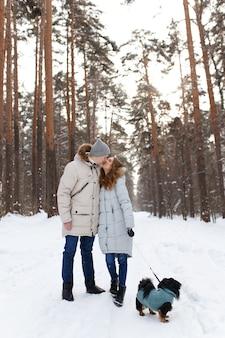 Влюбленная пара выгуливает собаку в зимнем лесу