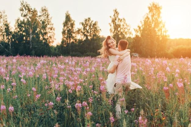 사랑에 빠진 커플이 꽃의 초원을 걷는다. 사랑과 봄이 피었습니다. 남자가 여자를 안다