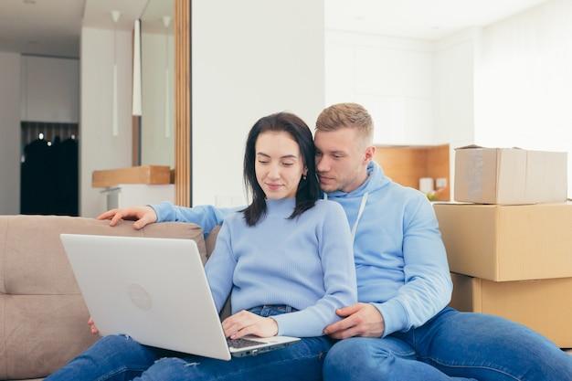 新婚夫婦に恋をし、新しいアパートに引っ越し、ラップトップを使って新しい家具を選ぶカップル