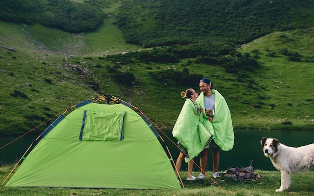 湖のほとりのテントの近くに、コーヒーやお茶を入れた暖かい毛布に包まれた恋愛中のカップルが立っています。山で犬と一緒に観光客のカップル。旅行、休暇、観光。