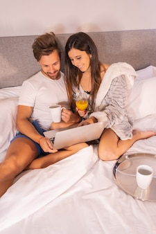 ホテルのベッドでの朝食、愛するカップルのライフスタイルでホテルやコンピューターからの旅行を探しているパジャマを着たカップル。