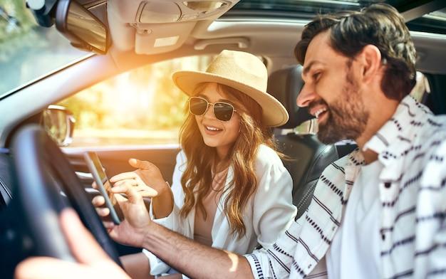 Парочка в машине смотрит в телефоне навигационные карты. покупка машины. путешествия, туризм, отдых.