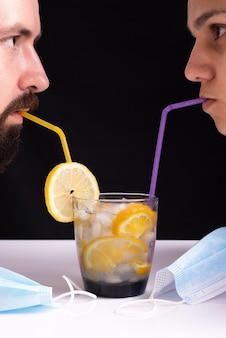 Пара девушки с парнем пьют коктейль из соломинок, снимая защитные маски от коронавируса. большой план.