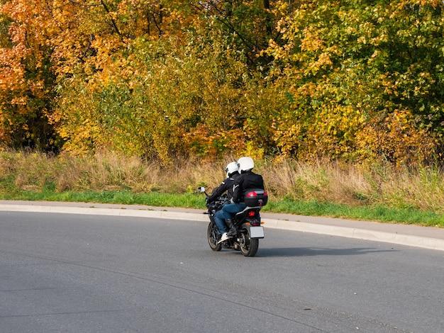 同じバイクに乗った数人のバイカーが秋の高速道路に乗っています。