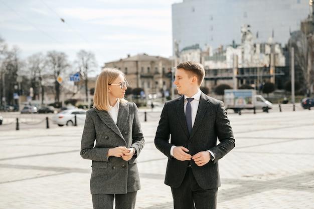 두 명의 비즈니스 사람들이 사무실 밖에서 사무복을 입고 도시를 걷고 있습니다.