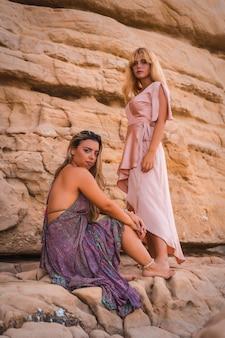 Пара кавказских девушек сидит на пляже в очень красивых платьях, наслаждаясь летом