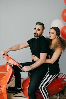 バイクでポーズをとるピエロのカップル