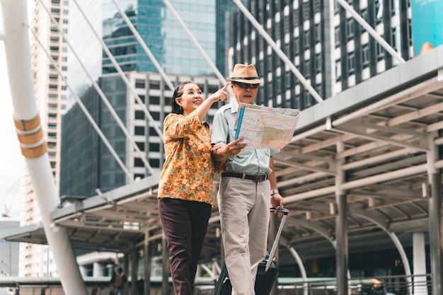 首都を楽しそうに訪れ、楽しんで地図を見て訪れたい場所を見つけるアジアの高齢の観光客のカップル。