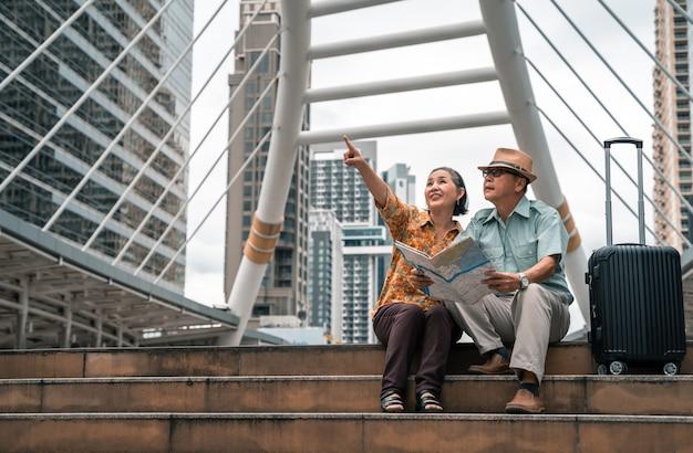 首都を楽しく訪れ、地図を見て訪れたい場所を探すアジアの高齢者のカップル。