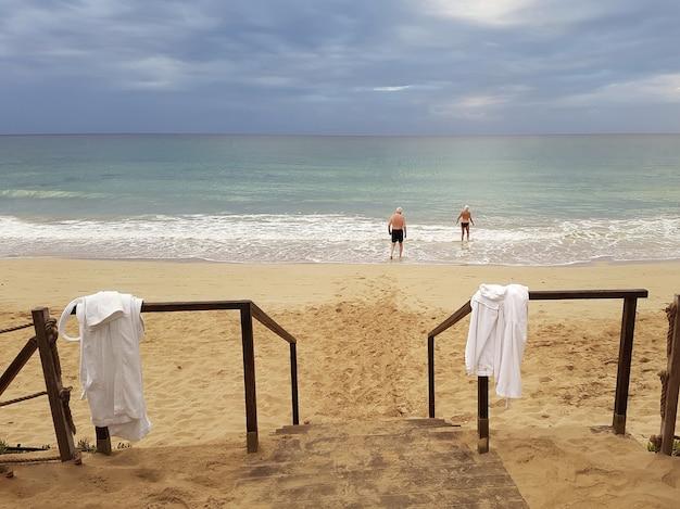 薄暗い空を背景に朝の海に数人の高齢者が泳ぎに行く