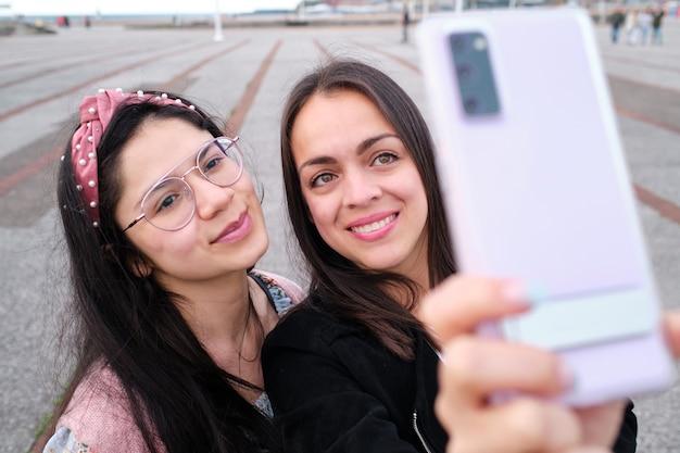 야외의 빈 주차장에서 셀카를 찍는 두 명의 여자 친구