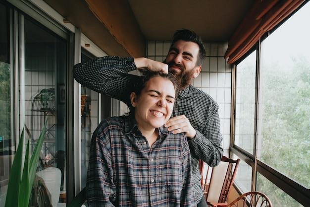 晴れた日の間に非常に明るいギャラリーで笑って楽しんでいる友人のカップル