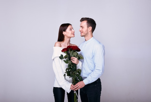 赤いバラの花束と白い背景でポーズをとる恋人のカップル。