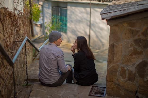 恋人のカップルが階段に座って、白い古い家のラブストーリーの背景で話します高品質の写真