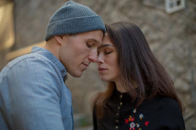 두 연인은 맑은 날씨 러브 스토리 고품질 사진에서 돌 집의 배경에 대해 서로 키스하기 위해 스트레칭