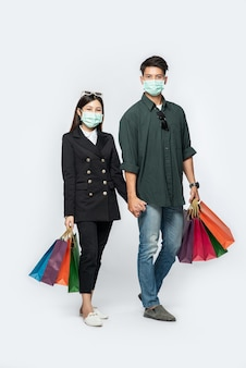 Пара мужчина и женщина в масках несли много бумажных пакетов в магазин