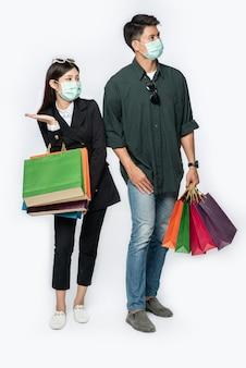 マスクを着用し、買い物にたくさんの紙袋を持っていた男女のカップル