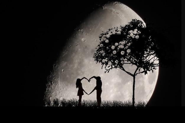 Пара влюбленных лун ночью, большая луна, мужчина и женщина составляют фигуру сердца
