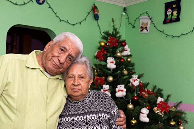 크리스마스 트리 앞에서 포즈를 취하고 웃고 있는 노인 부부